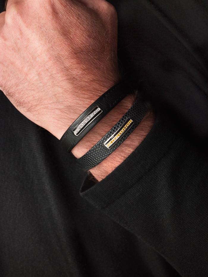 bracelet homme en lézard mat noir, barrette en or gris brillant, émail noir, diamants cognac et Modèle Precious : bracelet en veau noir lisse avec surpiqûre ton sur ton, émail noir, barrette en or gris brillant, diamants blancs.
