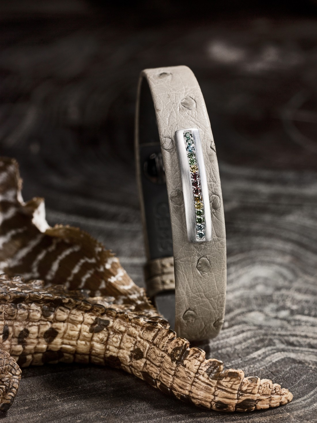 Bijou accessoire homme : Bracelet en autruche sable, barrette en or gris satiné brossé, sans émail, diamants multicolores.
