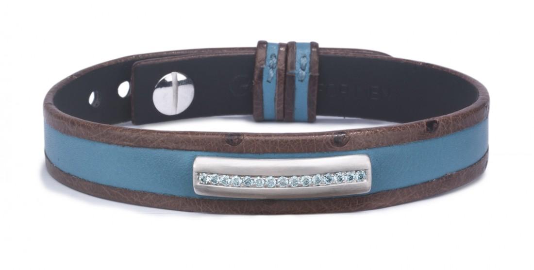 bracelet en cuir pour homme orné d'unebarrette en or brossé gris 18 kt sertie de diamants bleus ciel. Ce bracelet pour homme est monté sur bicolore combinant un veaubleu ciel à une autruche couleur chocolat.